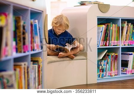 Child In School Library. Kids Read Books. Little Boy Reading And Studying