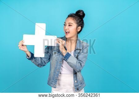 Happy Asian Woman Standing And Holding Plus Or Add Sign On Blue Background. Cute Asia Girl Smiling W