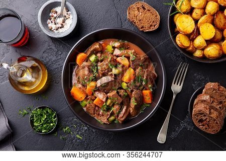 Beef Meat And Vegetables Stew In Black Bowl With Roasted Baby Potatoes. Dark Background. Top View.