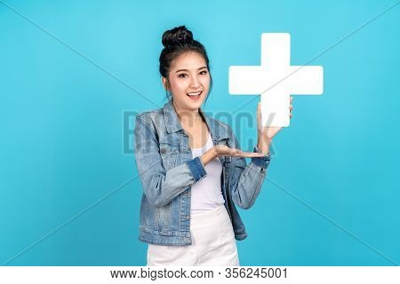 Happiness Asian Woman Smiling, Showing Plus Or Add Sign And Other Hand Open On Blue Background. Cute