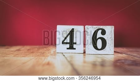 Number 46 On A Vintage Wooden Table And Dark Maroon Background - Retro Style White Blocks
