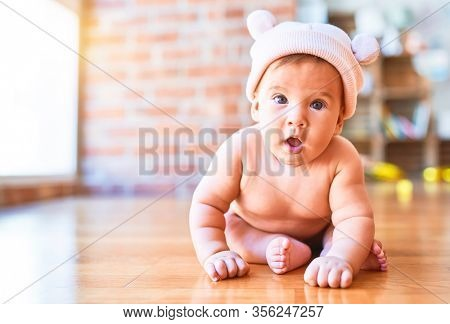 Adorable baby lying down on the sofa at home. Newborn wearing fanny hat relaxing and resting comfortable