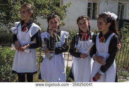 Rushon, Tajikistan - June 17, 2020: Four School Children, Girls, In School Costume In Front Of The S