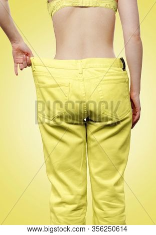 A Caucasian Woman Shows The Results Of Her Weight Loss By Pulling Off Wide-waisted Yellow Jeans. Iso