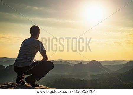 With Reconciliation Confident Man Sitting On The Edge. Amazing View To Born New Day In Hilly Landsca
