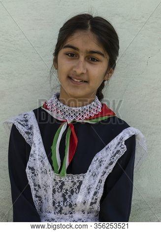 Rushon, Tajikistan - June 17, 2020: School Girl In School Costume With Flowers In Front Of The Schoo