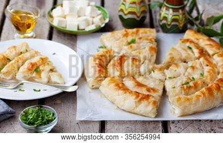 Traditional Feta Cheese Phyllo Pastry Pie, Banitsa. Wooden Background.