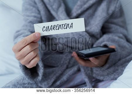 closeup of a man, wearing a gray robe staying at home or a hotel room, showing a note with the word cuarentena, quarantine in spanish written in it