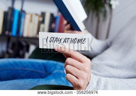 closeup of a man, in casual wear reading a book and showing the message I stay at home written in a piece of paper, as a measure to stop the spreading of the covid-19