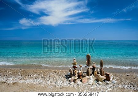 Concept of balance and harmony. Stones pebbles stacks on the beach coast of the blue sea in the nature. Meditative art of stone stacking.