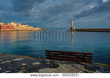 Bench in picturesque old port of Chania is one of landmarks and tourist destinations of Crete island in the morning on sunrise. Chania, Crete, Greece