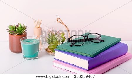 Books Stack, Eyeglasses, House Plants Succulents And Fragrant Candle And Sticks. Background For Worl
