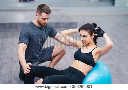 Personal Trainer Training His Client In The Gym. Shot Of A Personal Trainer Training His Client In T