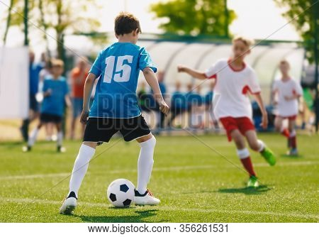 School Soccer Boys Playing Tournament Match. Children Play Outdoor Sport On A Sunny Day. Junior Leve