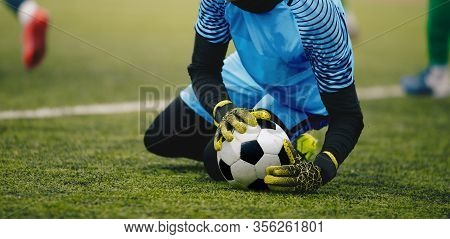 Soccer Football Goalkeeper Catching Ball. Goalie In Action On The Pitch During Match. Goalkeeper In
