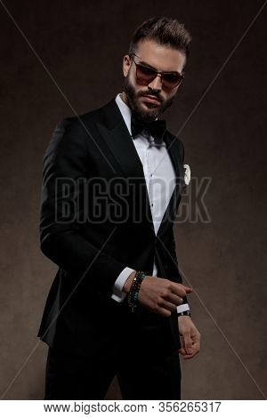 Tough fashion groom looking forward while wearing suit and sunglasses, standing on a wallpaper studio background