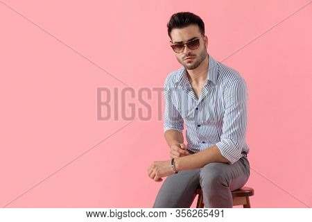 Tough smart casual man looking forward while wearing sunglasses and shirt, sitting on a stool on pink studio background