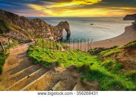 Durdle Door at the beach on the Jurassic Coast of Dorset at sunset, UK