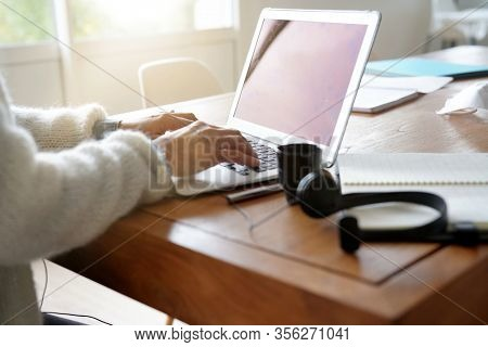 Closeup of woman hands typing on laptop, home-office