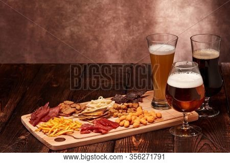 Three glasses with different beer and set of various kind snacks: jerky,  potato chips, salted nuts, stockfish, bread spicy crackers, dried squids on wooden table on brown background. Snacks for beer.