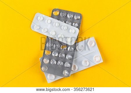 A Pile Used Blister Packs Of Pills On Yellow Background. Medical Blisters Packs Opened And Empty Wit