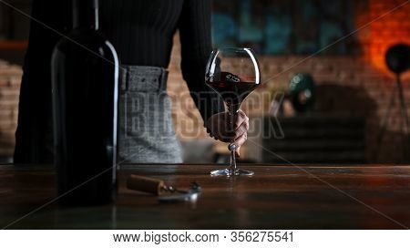 Woman tasting and drinking red wine from wine from elegant wine glass at home in a cosy dark room.