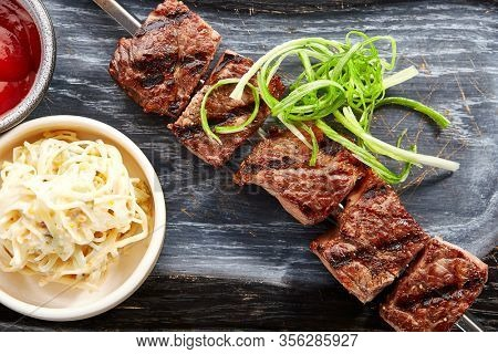 Marbled beef skewer top view. Delicious kebab with sauce and noodles on wooden tray. Grilled meat with tasty garnish. Spicy meal with onion. Restaraunt dish, roasted food composition