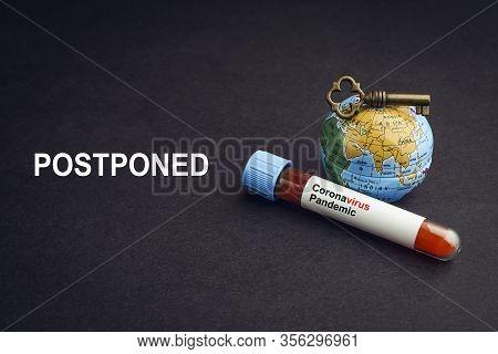 Coronavirus Postponed Text With World Globe, Key And Blood Test Vacuum Tube On Black Background. Cov
