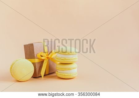 Yellow Macarons With Gift Box On A Peach Pastel Background. Lemon Macarons. Place For Text.