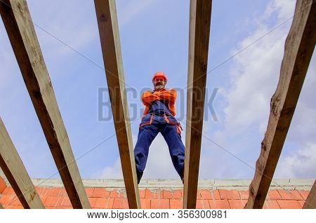 Construction Worker On Construction Site. Roofer Carpenter Builder Working On Roof Structure On Cons