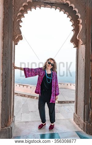 Stylish Woman Tourist Poses In An Arched Doorway Of The Monsoon Palace In Udaipur India
