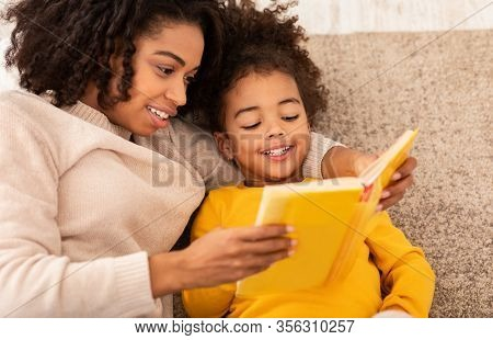 Cute Black Mother And Little Daughter Reading Book Together Sitting On Couch At Home. Bedtime Story