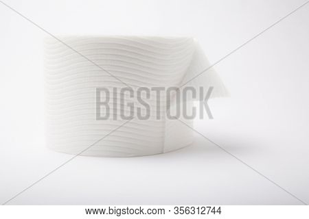 A single roll of white bathroom  toilet paper with a flipped edge on a white dreamlike background, horizontal landscape orientation with high-key lighting.
