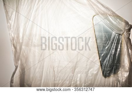 A thin plastic sheet hanging on a wall that covers an asymmetrical mirror in a high contrast, conceptual abstract grunge style.