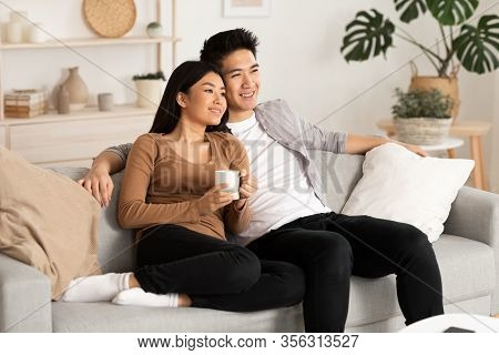 Home Weekend. Lovely Filipino Couple Watching Film Resting On A Couch At Home, Copy Space