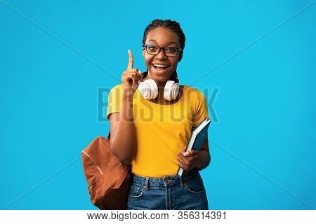 Great Idea. Excited Black Student Girl Pointing Finger Up Having Eureka Moment Standing On Blue Stud
