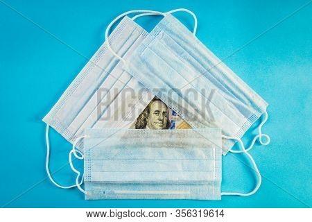 Three Medical Masks Lie On 100 Dollars Banknote On Blue Background. Concept Of Deficit, Speculation