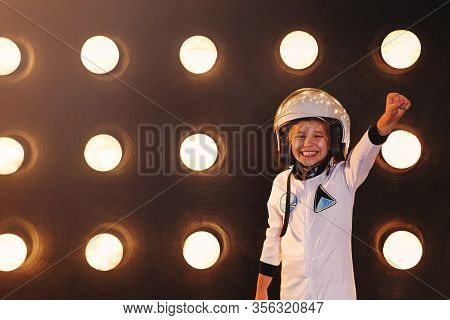 Cheerful Excited Child In White Spacesuit And Helmet Standing With Arm Raised Against Spaceship Wall