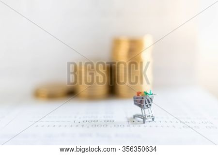 Business E-commerce And Money Concept. Close Up Of Shopping Cart Or Trolley Miniature Figure On Bank