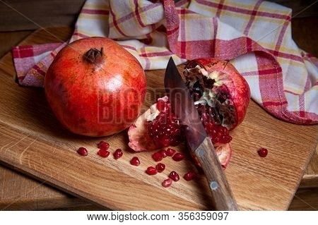 Fresh Red Pomegranate With Vintage Knife On A Wooden Background..