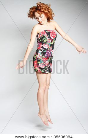 Young charming female in dress jumping over white background poster