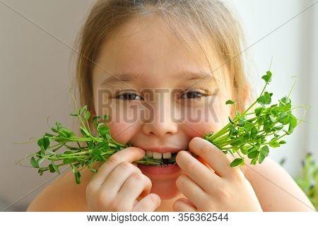 Happy Girl Eats Pea Microgreen .vegeterian Concept.good Appetite. Spring Avitaminosis.sprout Vegetab