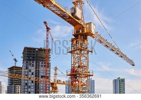 Several Construction Tower Cranes Of Different Heights At A Building Site During The Construction Of