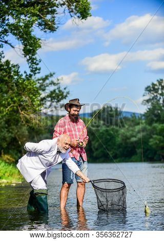 Bearded Man And Brutal Hipster Fishing. Fishing Team. Friends Catching Fish. Hobby And Recreation. C