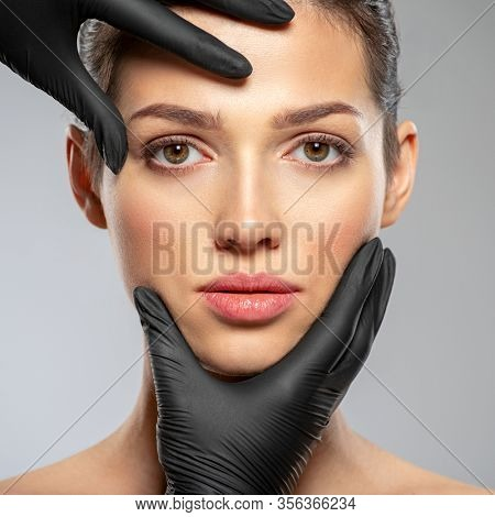 Plastic surgery doctor is touching face of a patient by hands. Face skin check before plastic surgery. Beautician touching woman face. Doctor checks a skin before plastic surgery. Beauty treatments.