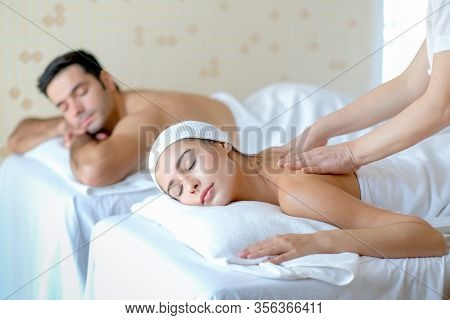 Young Woman Enjoy Massage With Her Couple Man Who Lie Beside In Spa Room With Day Light.