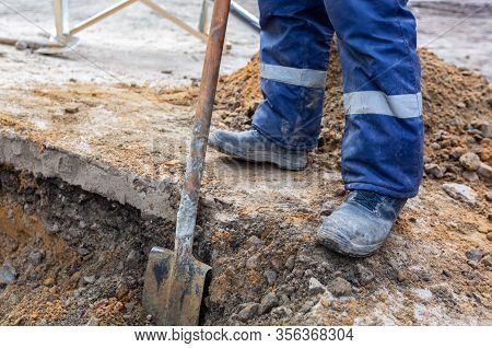 Worker In Dirty Uniform And Shoes With Shovel Is Digging A Pit On Construction Site. Concept Of Hard