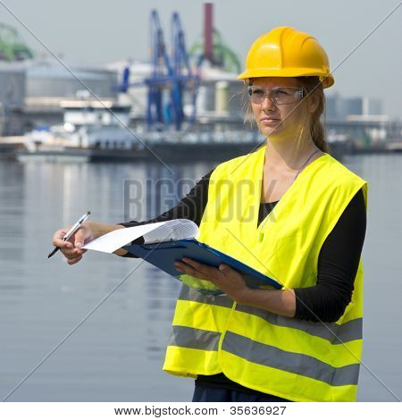 Female foreman turning a page on her clip board during her inspection rounds through an industrial harbor poster