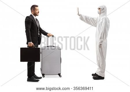 Full length profile shot of a man in a white decontamination suit gesturing stop to a businessman with a suitcase isolated on white background