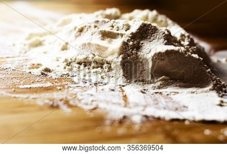 A Heap Of Flour On A Wooden Board Ready To Be Kneaded And Baked. Preparation Of Flour-based Foods Be